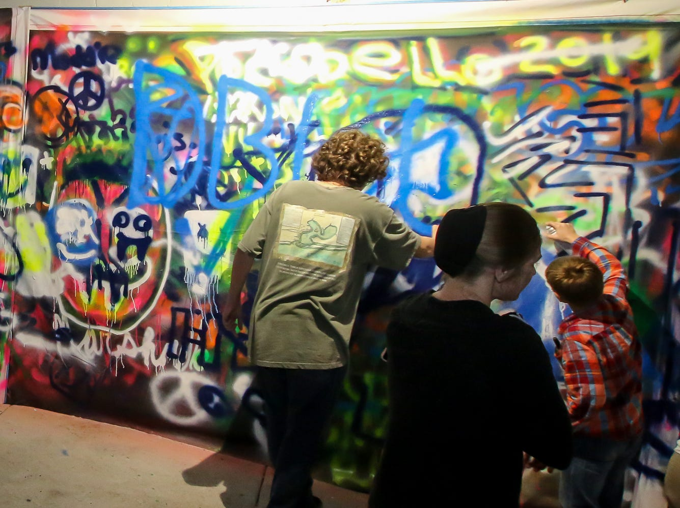 People spray paint on Zarzaur Law's Legal Graffiti wall during Gallery Night on Friday, February 22, 2019.