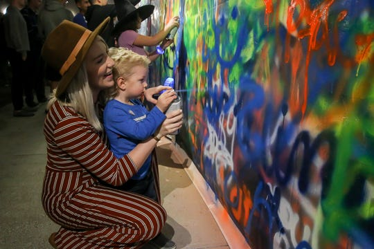 People spray paint on Zarzaur Law's Legal Graffiti wall during Gallery Night on Feb. 22.