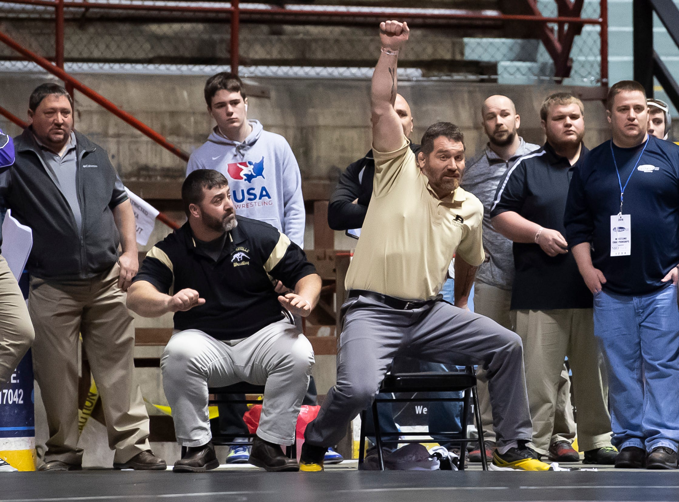 Biglerville head coach Ken Haines raises his arm as Eli Tuckey defeats Newport's Dorian Gonzalez during a 132-pound semifinal bout at the District 3 wrestling championships at Hersheypark Arena Saturday, February 23, 2019. Tuckey won by decision 3-2.