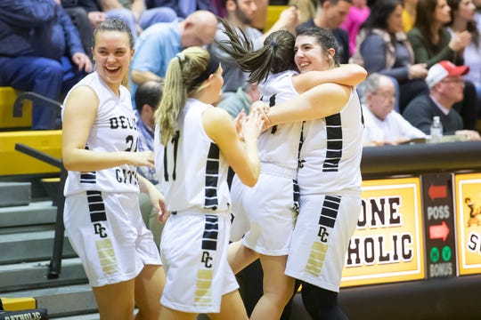 Delone Catholic's Bradi Zumbrum, far right, hugs Dee McCormick as the Squirettes defeat Susquenita 70-35 in the semifinals of the District 3 3-A playoffs Friday, February 22, 2019. Delone Catholic will play against Trinity for the championship on Wednesday.