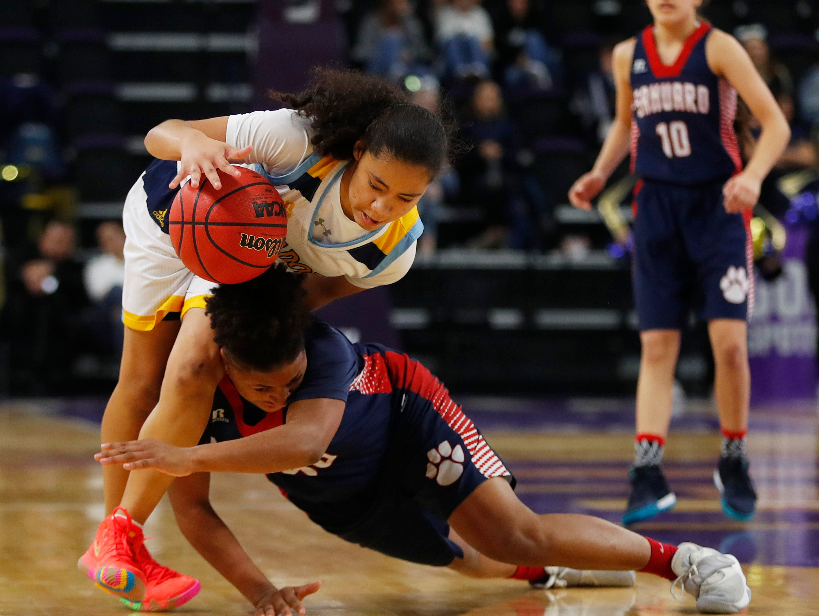 Sahuaro's Lilly Watson (50) dives into the legs of Shadow Mountain's Senya Rabouin (2) during second half of the 4A girls basketball semifinal game at Grand Canyon University Arena in Phoenix, Ariz. on February 22, 2019.
