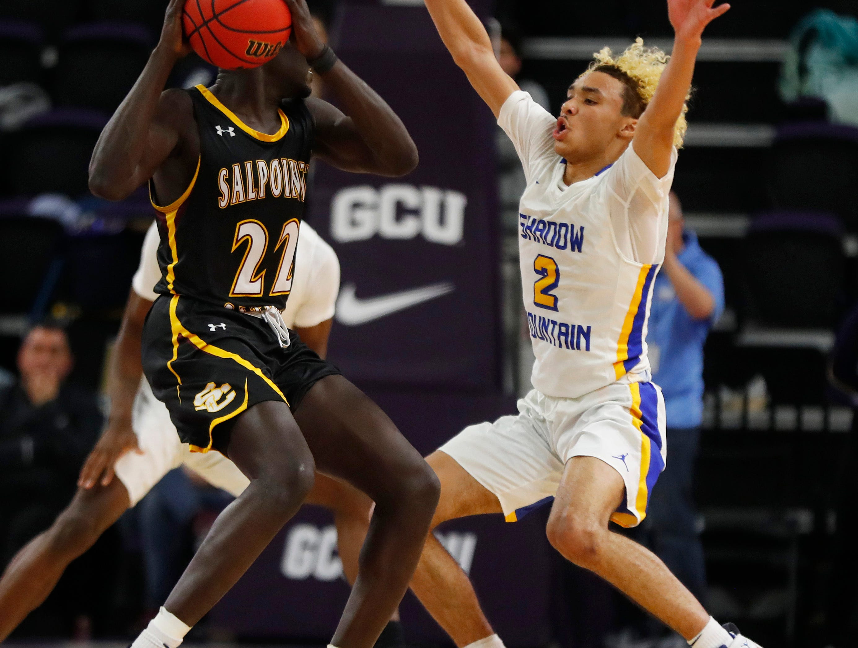 Salpointe Catholic's Majok Deng (22) travels under defensive pressure from Shadow Mountain's Jaelen House (2) during first half of the 4A boys basketball semifinal game at Grand Canyon University Arena in Phoenix, Ariz. on February 22, 2019.