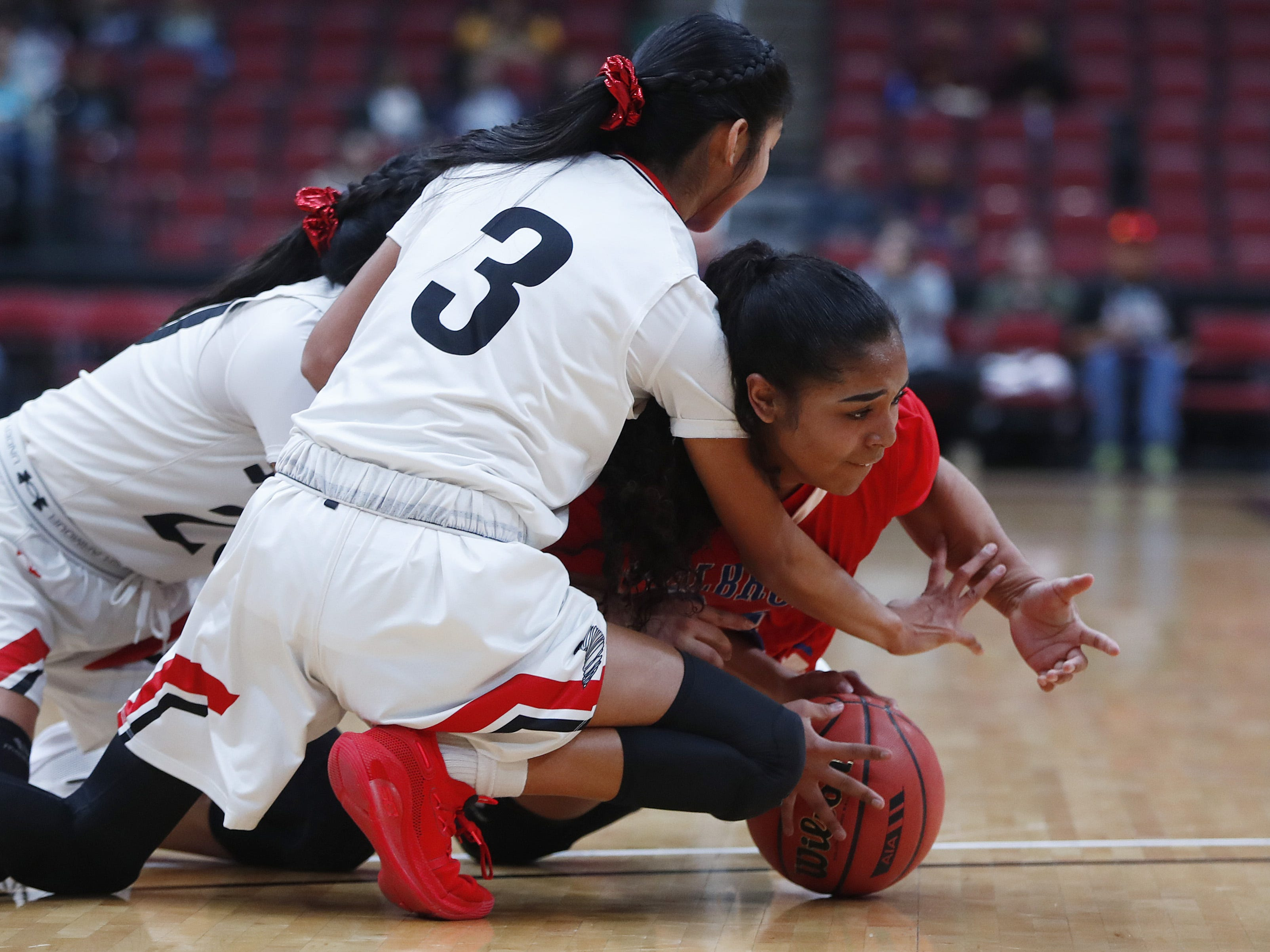 Holbrook's Madison Chappell (24) looses a ball on the floor under pressure from Page's Myka Taliman (20) and Miquedah Taliman (3) during the first half of the 3A girls basketball state championship at Gila River Arena in Glendale, Ariz. on February 23, 2019.