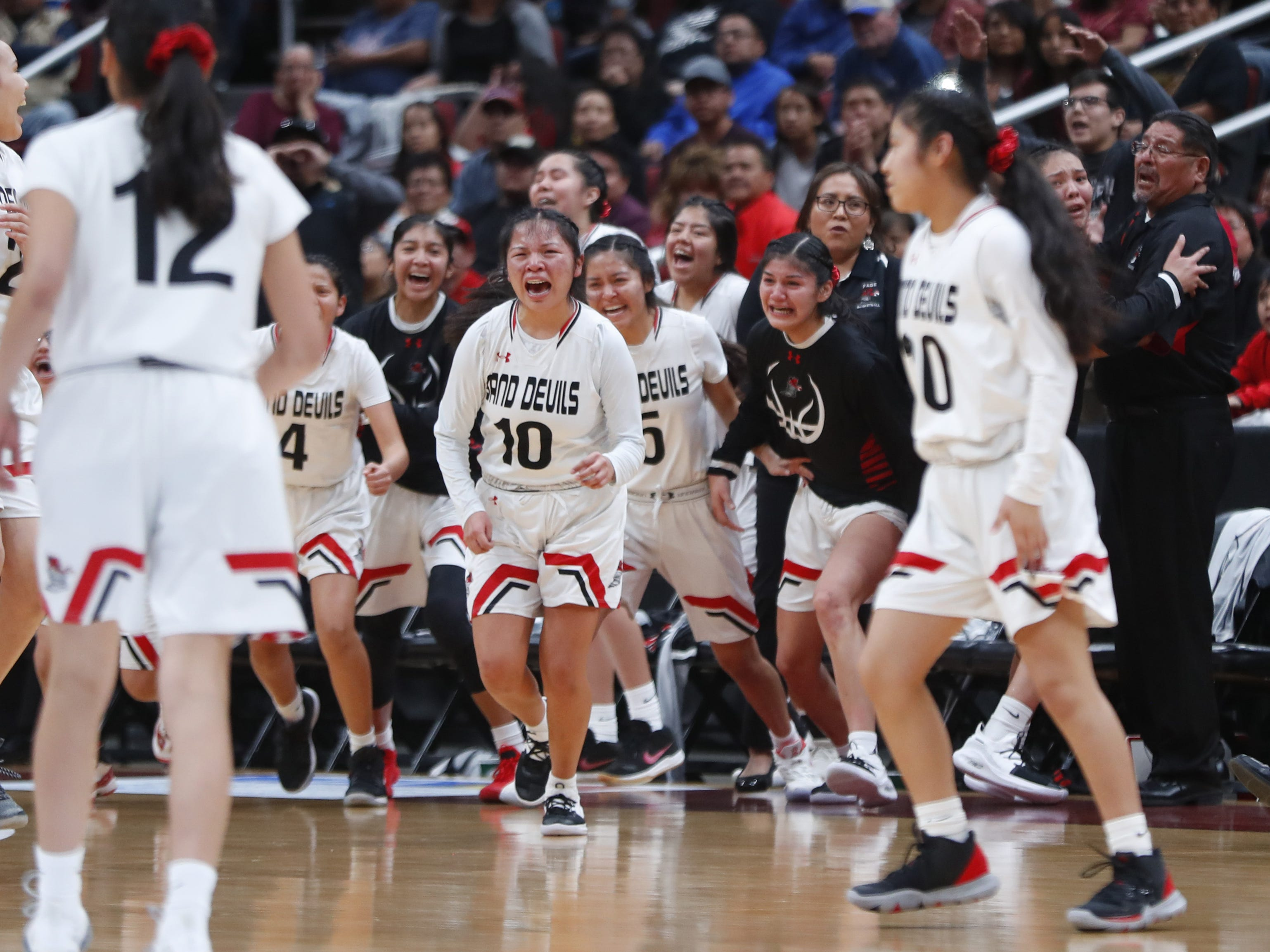 Page's Mikala Benally (10) charges the court with her teammates after winning the 3A girls basketball state championship game over Holbrook at Gila River Arena in Glendale, Ariz. on February 23, 2019.