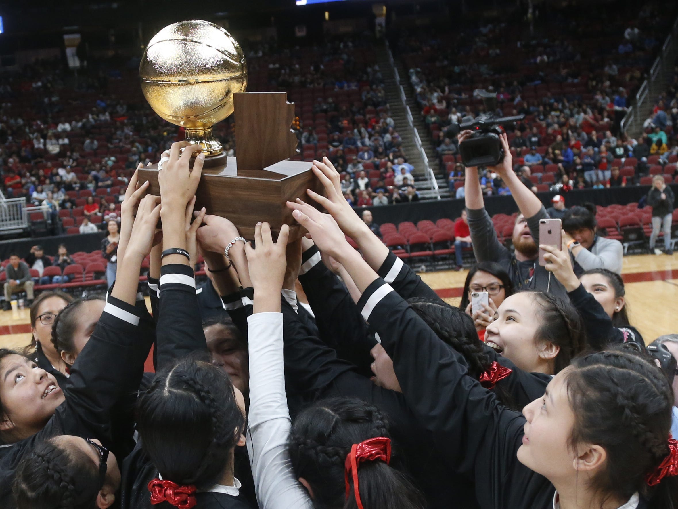 Page celebrates lifting the championship trophy after winning the 3A girls basketball state championship game over Holbrook at Gila River Arena in Glendale, Ariz. on February 23, 2019.