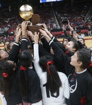 Page's girls basketball team lifts the championship trophy on Saturday at Gila River Arena.