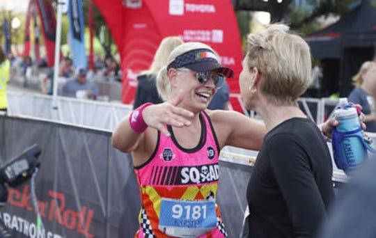 Sen. Kyrsten Sinema hugs triathlon great Paula Newby-Fraser after completing the Rock 'n' Roll Arizona half marathon on Jan. 20. Sinema is competing Ironman New Zealand on March 2.