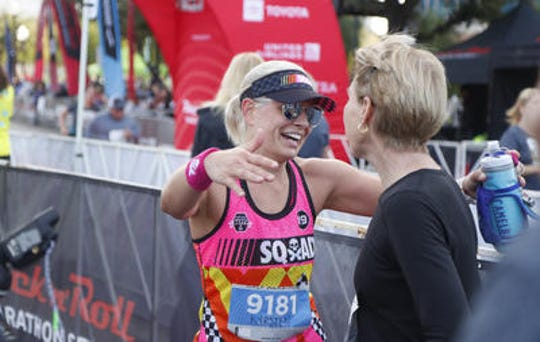 Sen. Kyrsten Sinema hugs triathlon great Paula Newby-Fraser after completing the Rock 'n' Roll Arizona half marathon on Jan. 20. Sinema is competing Ironman New Zealand on March 2.