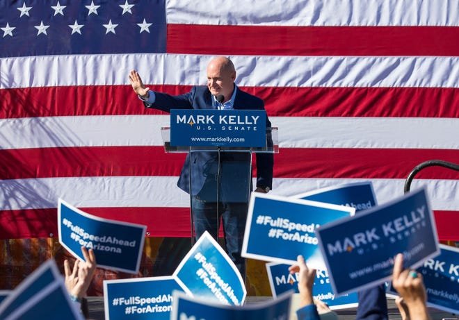 Mark Kelly waves to the crowd after officially kicking off his U.S. Senate campaign at an event at Hotel Congress, Feb. 23, 2019, in Tucson, Ariz. The former astronaut is the husband of former congresswoman Gabrielle Giffords.
