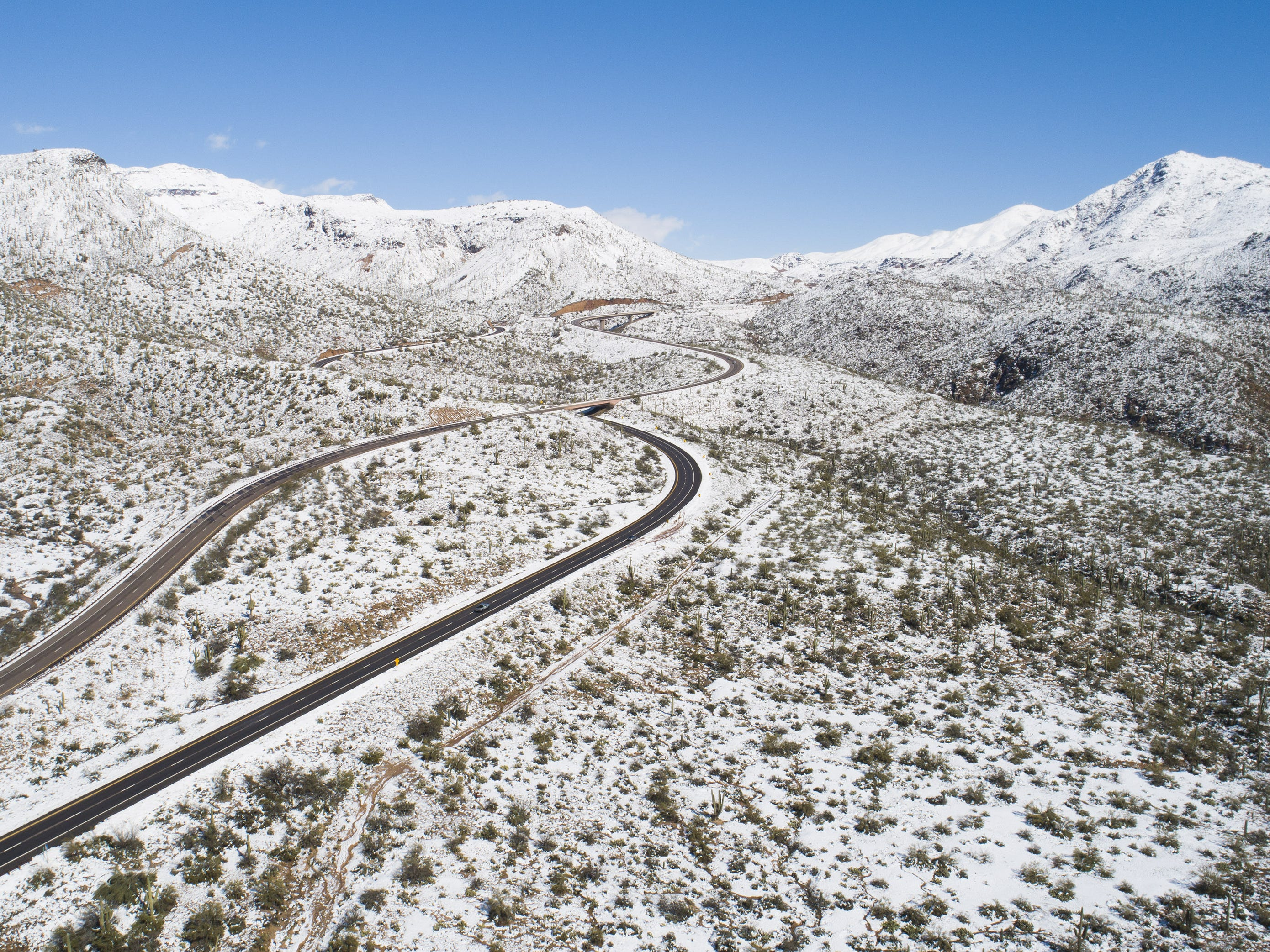 Cars drive along State Route 87 as snow covers the desert in the Tonto National Forest near Sunflower, Ariz. Feb. 23, 2019.