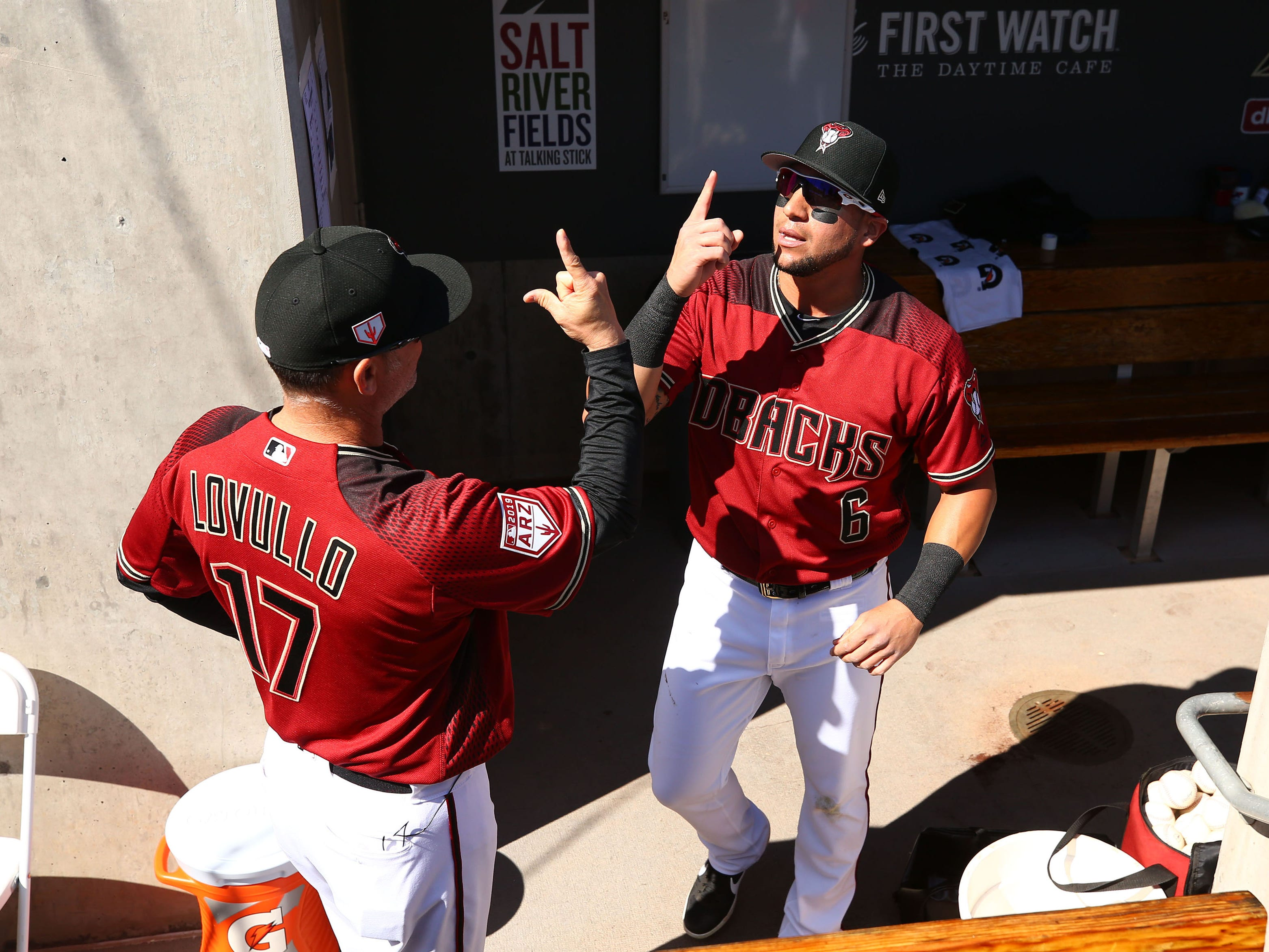 Arizona Diamondbacks manager Torey Lovullo and outfielder David Peralta react before playing the Colorado Rockies during a spring training game on Feb. 23, 2019 at Salt River Fields in Scottsdale, Ariz.