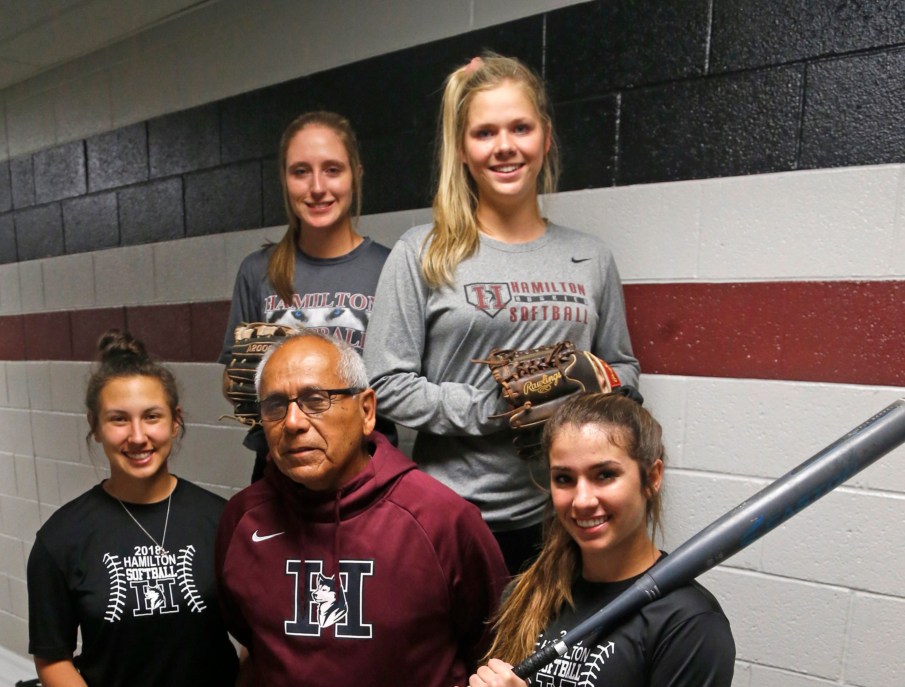 Hamilton's head coach Rocky Parra surrounded by his players Lorena Vasquez-Inzunza (L-R), Dani Cole, Macy Simmons and Loganne Stepp pose for a picture at Hamilton High School in Chandler, Ariz. on February 21, 2019.