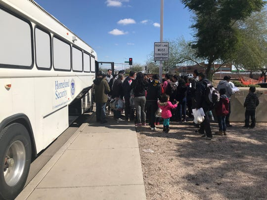 U.S. Immigration Customs Enforcement agents drop off a group of migrant families at a Greyhound station in Phoenix on Feb. 23, 2019.