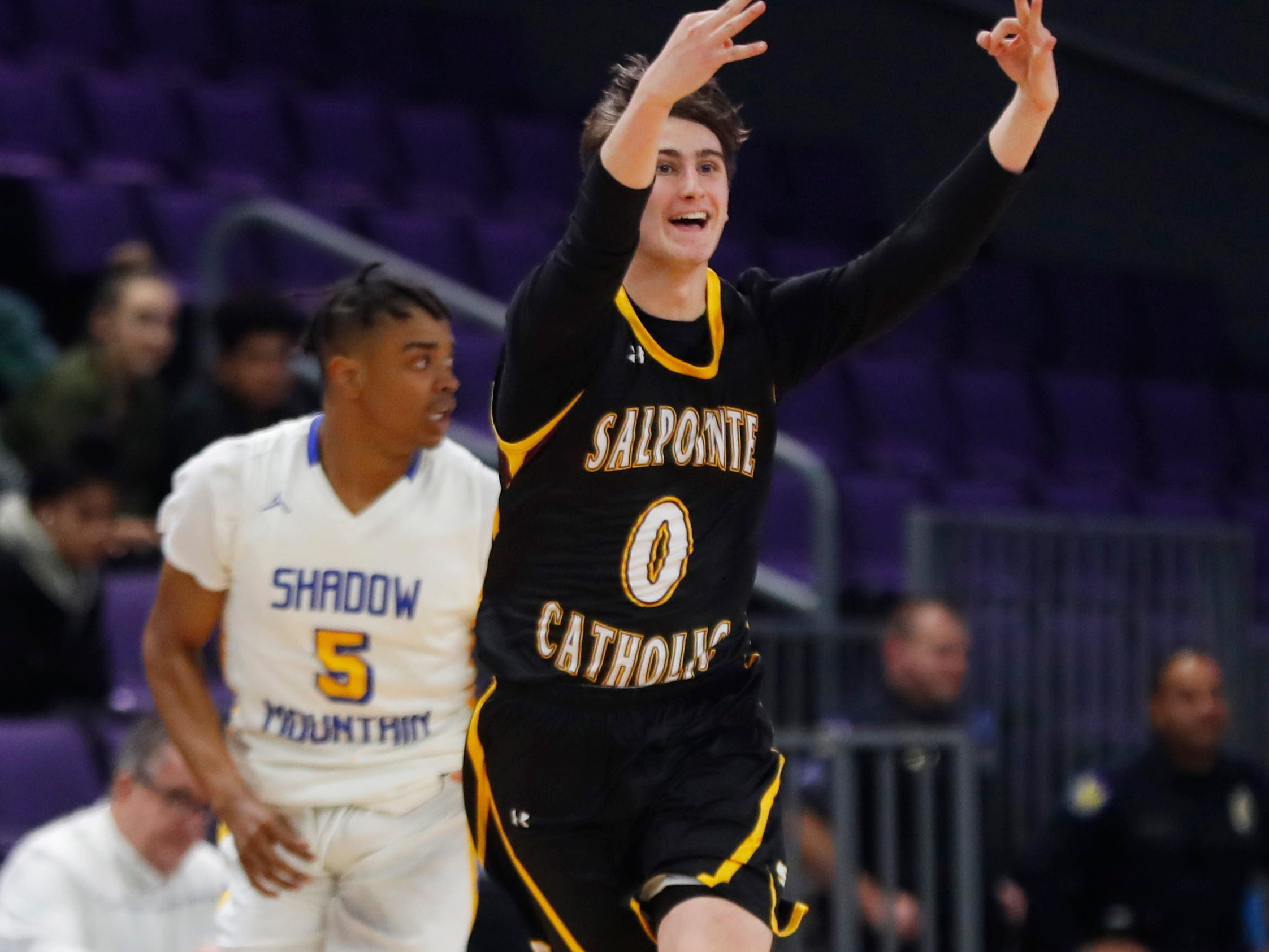 Salpointe Catholic's Luc Rosenblatt (0) celebrates hitting a three over Shadow Mountain's Christian Allen (5) during first half of the 4A boys basketball semifinal game at Grand Canyon University Arena in Phoenix, Ariz. on February 22, 2019.