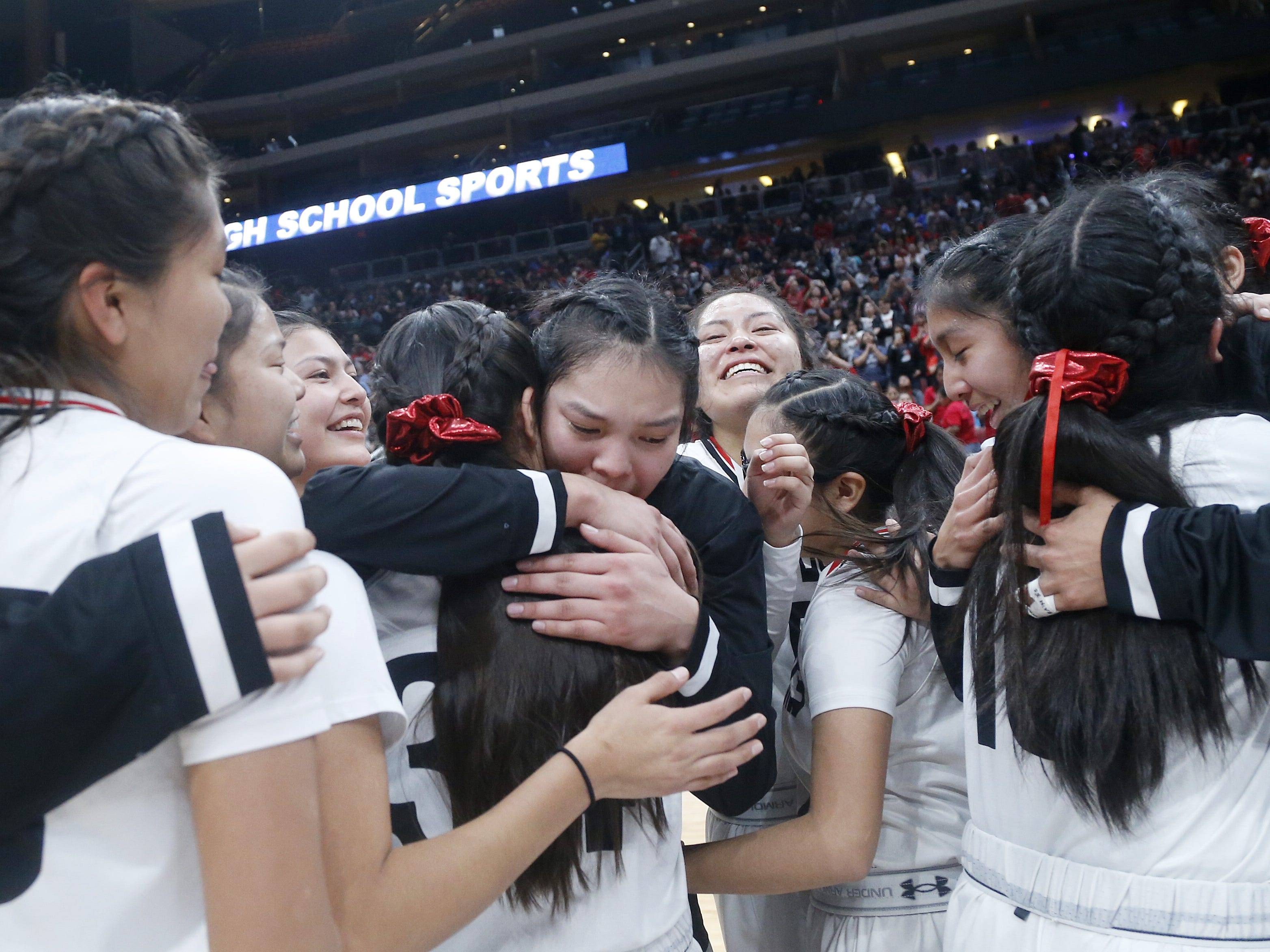 Page's Myka Taliman (20)(center) hugs her teammate Diana Secody (14) after winning the 3A girls basketball state championship game over Holbrook at Gila River Arena in Glendale, Ariz. on February 23, 2019.