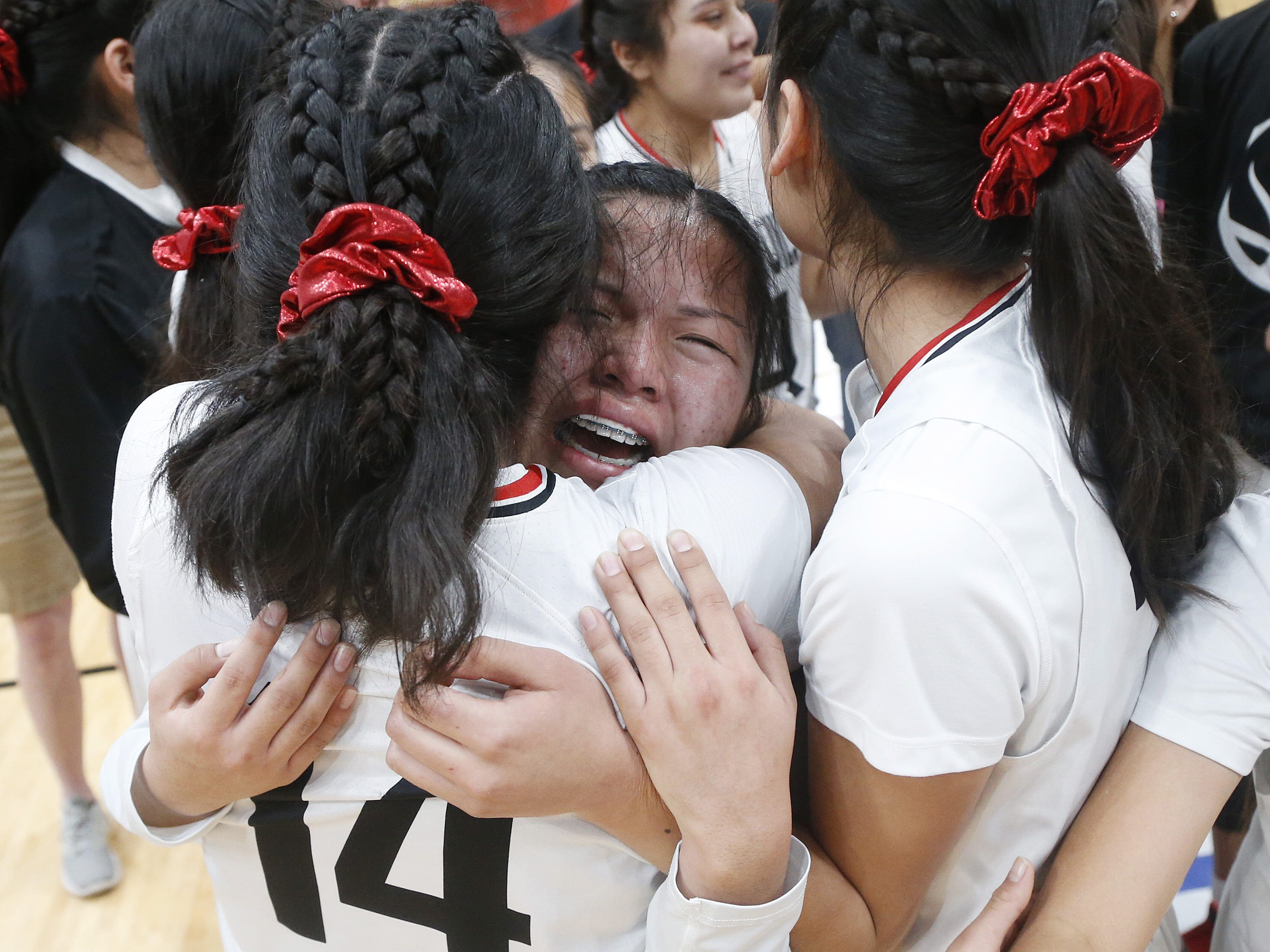 Page's Mikala Benally (10) hugs her teammate Diana Secody (14) after winning the 3A girls basketball state championship game over Holbrook at Gila River Arena in Glendale, Ariz. on February 23, 2019.