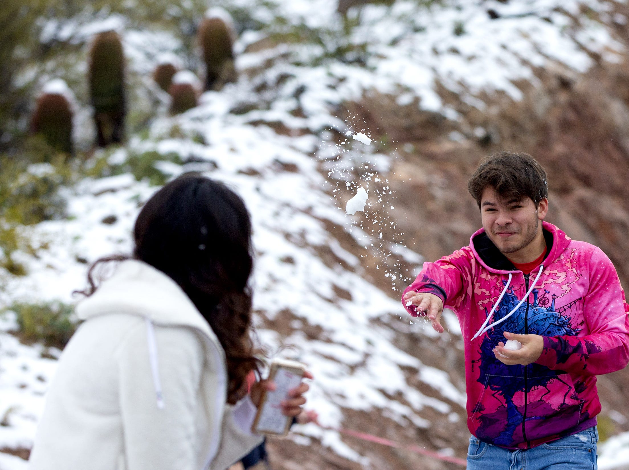 Marco Medina, 18, throws a snowball at Ana Montes, 18, after a winter storm brought snow to Fountain Hills.