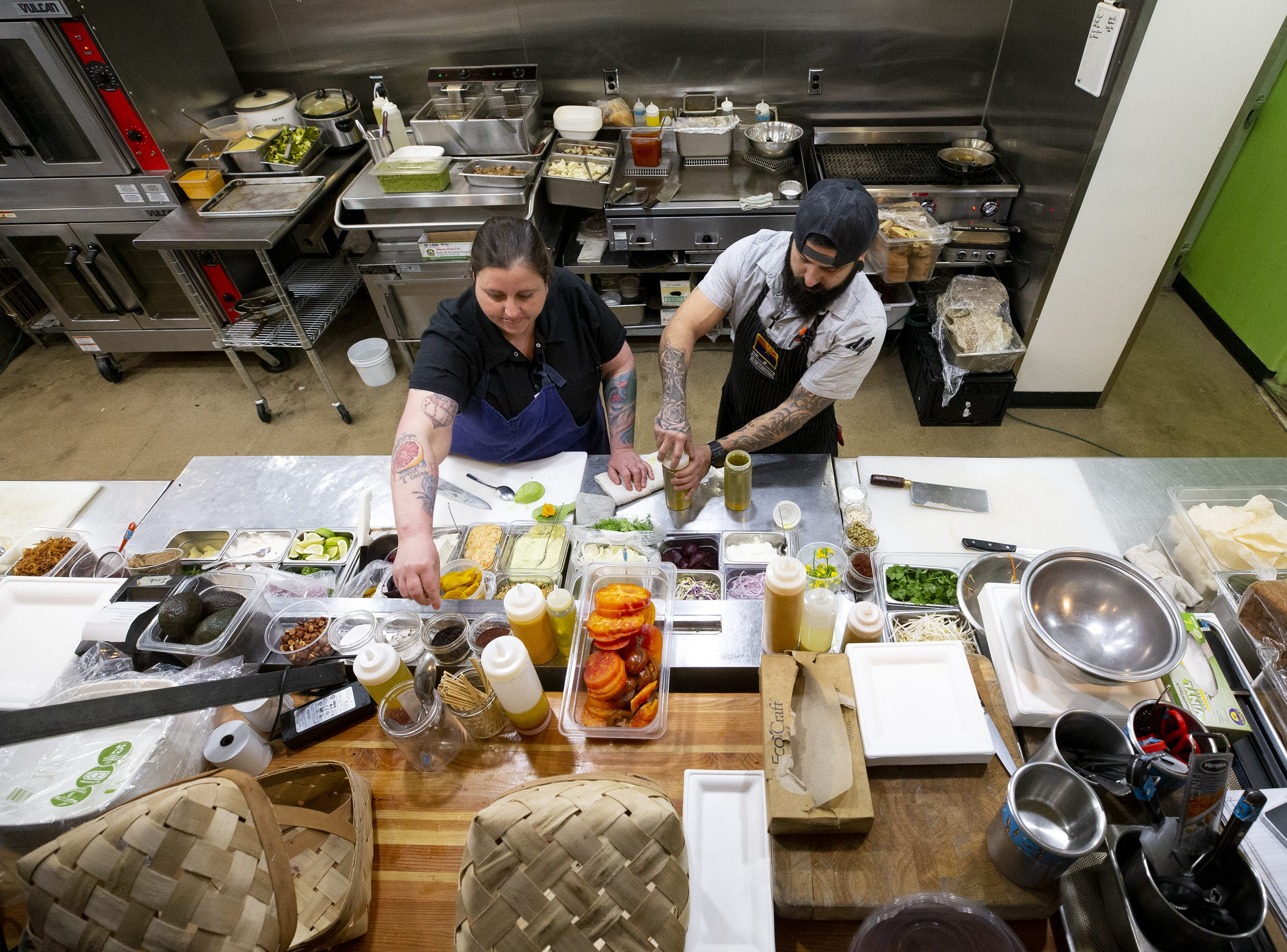 Singh Meadows chef Sacha Levine and cook Carlos Carbajal work in the Tempe kitchen.
