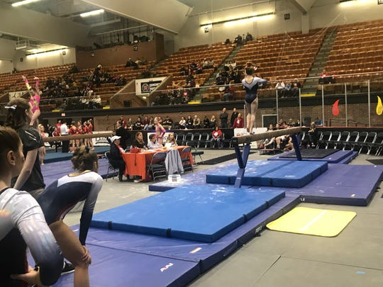 The All-American Flames gymnastics team looks on as one of its members competes on the balance beam.