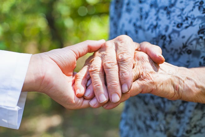 A close up photo of a medical doctor holding an elderly female's trembling hands. (Ocskay Mark/Dreamstime/TNS)