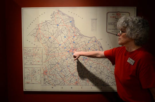 In this file photo from 2012, Lila Fourhman-Shaull, director of library and archives for York County Heritage Trust, shows a map of local war memorials.