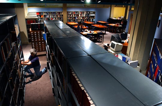 Then an assistant librarian and archivist at the York County Heritage Trust, Lila Fourhman-Shaull refiles books in the expanded library in this York Daily Record file photo from 2003.