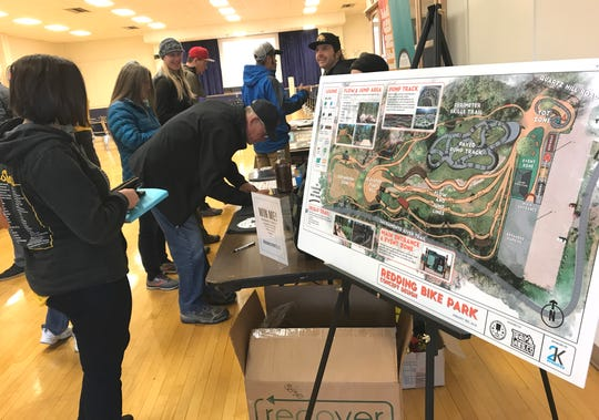 Rachel Hatch of the McConnell Foundation stands next to a concept design for the Redding Bike Park on Saturday during the first Jefferson State MTB Summit at the Veterans Memorial Building.