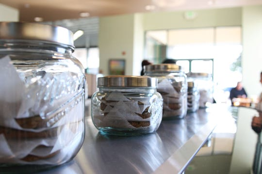 Mason jars full of cookies line the top of the pastry case.