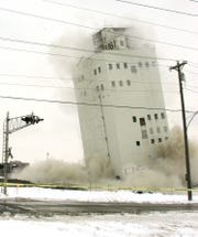 The Zip Feed Tower falls about 25 feet December 3, 2005. It was scheduled to be completely leveled, but was still standing after the blast.