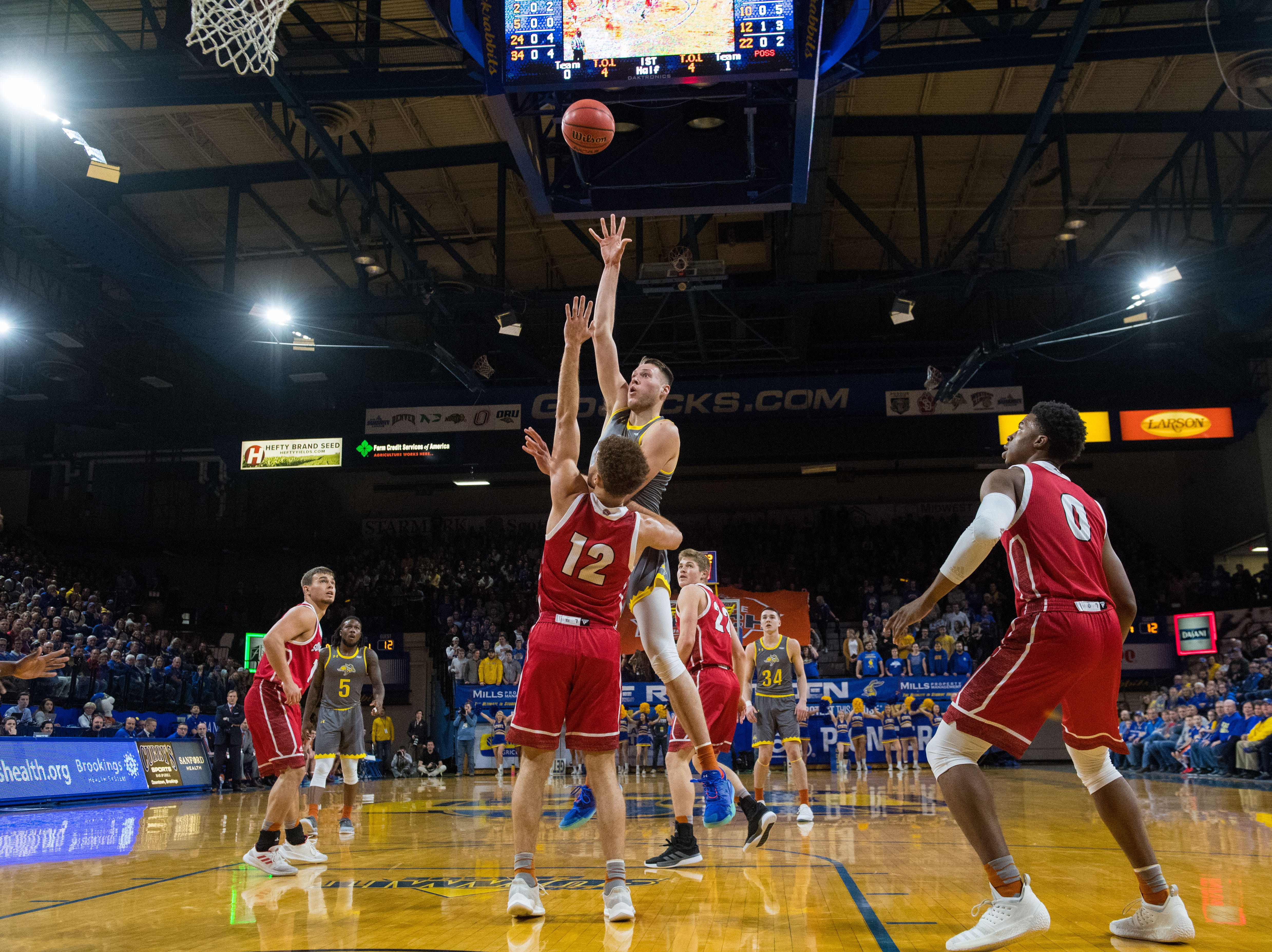 SDSU's Mike Daum (24) shoots the ball over USD players during a game, Feb. 23, 2019 in Brookings, S.D.