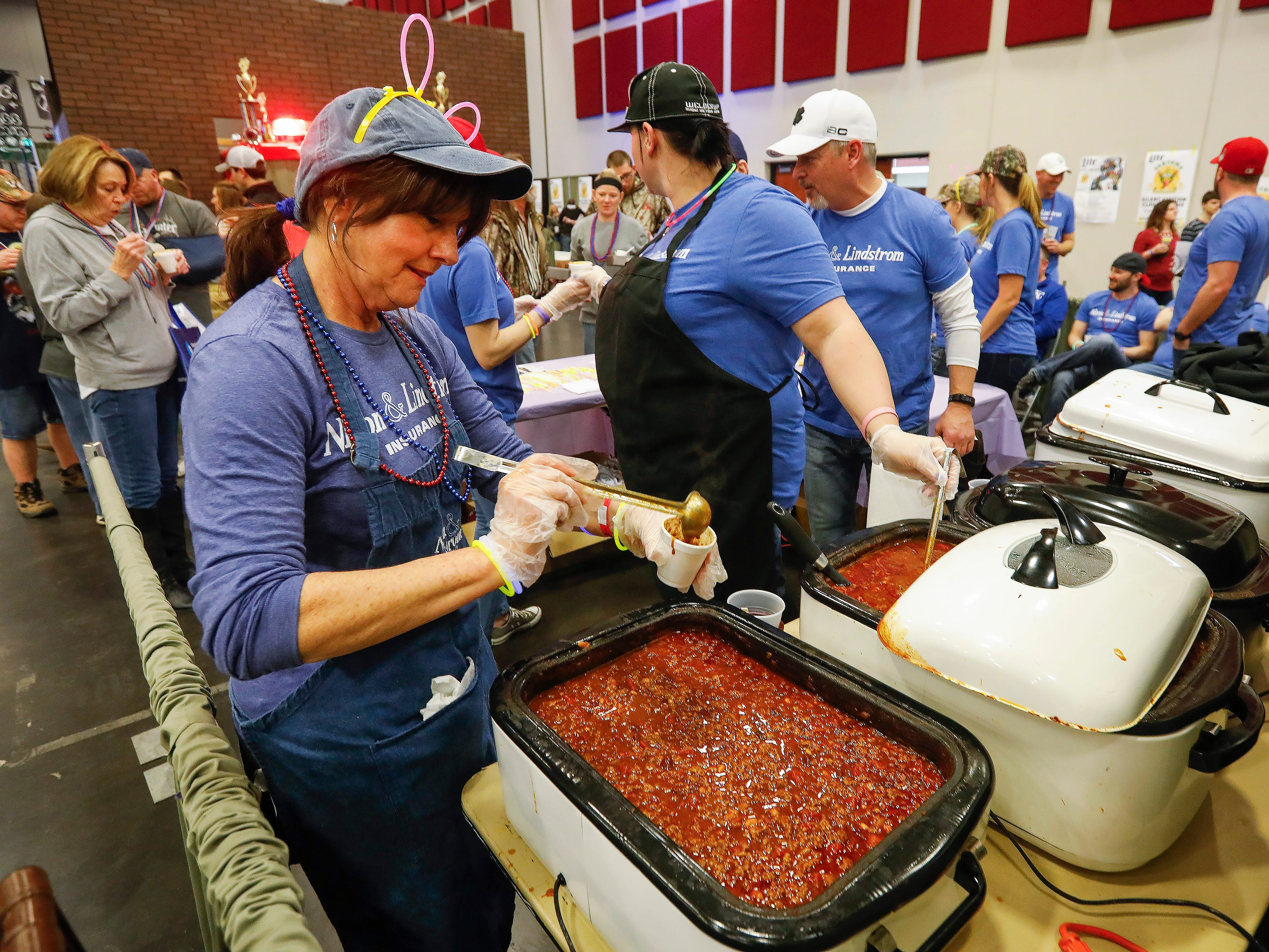 Sue Hawkins dishes out a sample of chili during the 2019 Sertoma Chili Cook-Off at the Springfield Expo Center on Saturday, Feb. 23, 2019.
