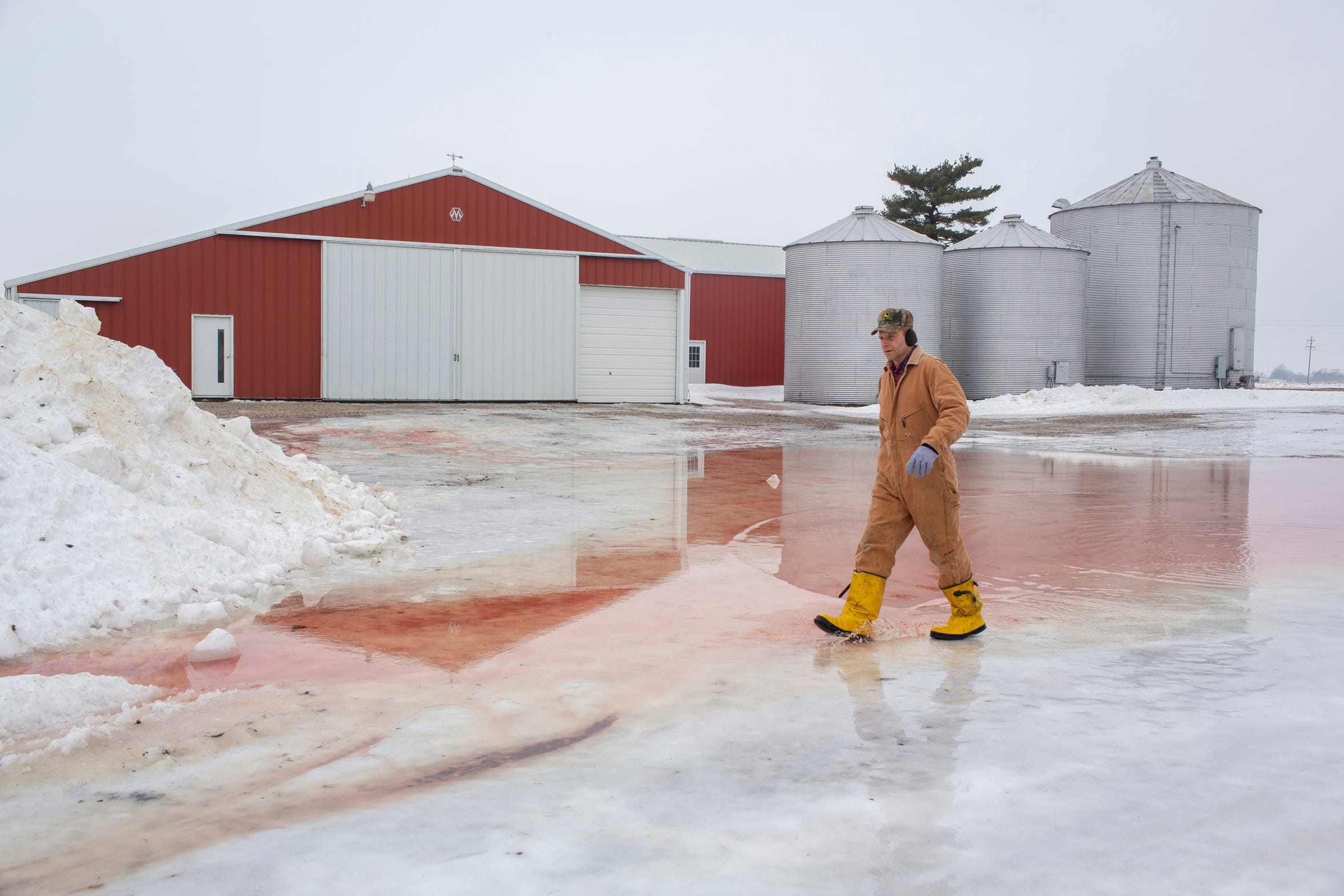 Randy DeBaillie walks over a sheet of ice at his farm in Orion, Illinois on February 3, 2019.He recently installed a small solar system to power his farm.