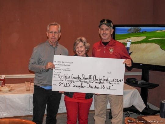 John Green of St James Bay Golf Club and Betty Kellum present Sheriff AJ Smith with a check for $5,155.47.