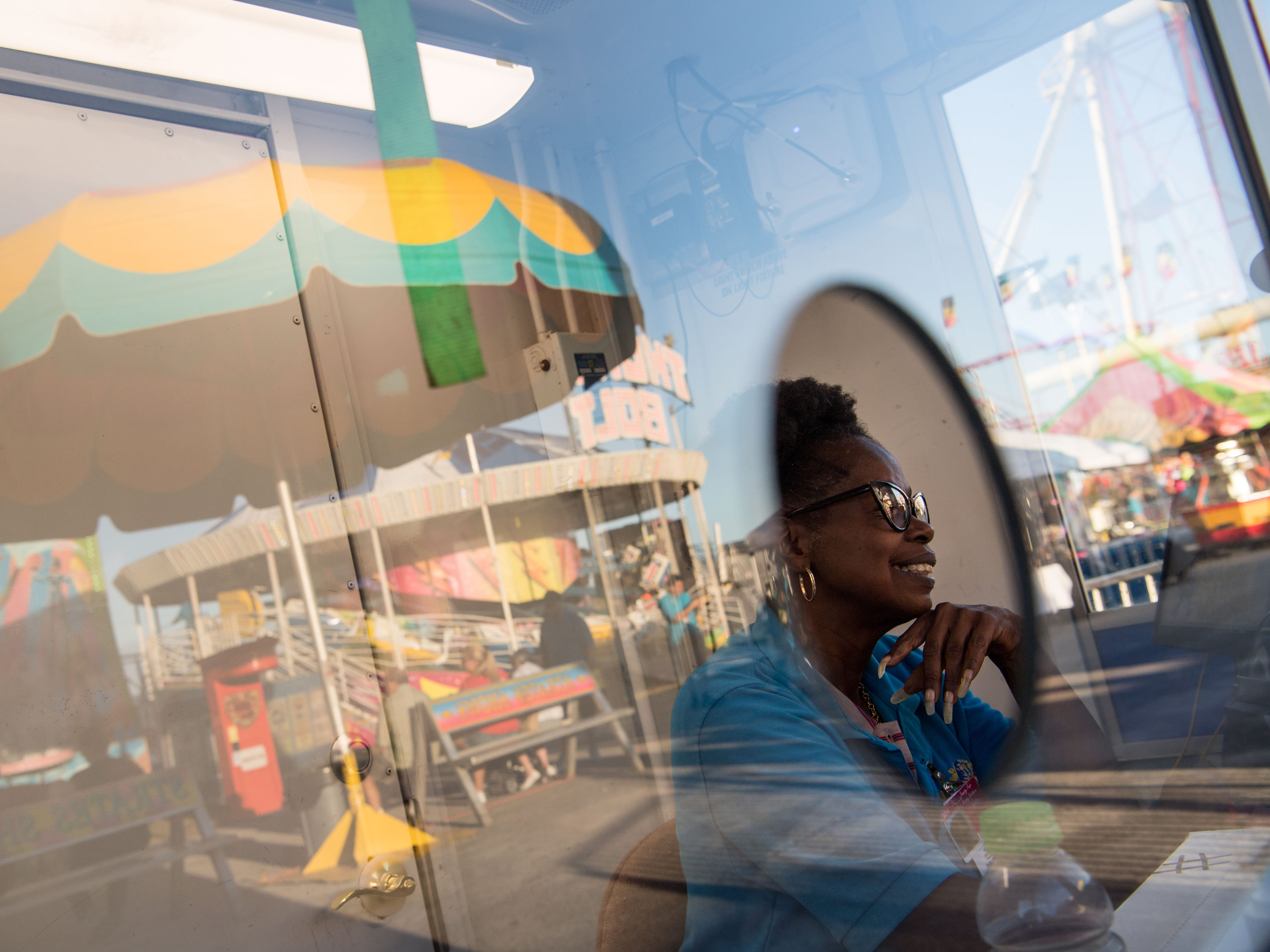 Strates Shows employee Helen Brooks, of Fort Pierce, enjoys music from nearby rides as she works behind the window at a tickets booth at the 54th annual St. Lucie County Fair on opening night Friday, Feb. 22, 2019, in Fort Pierce.