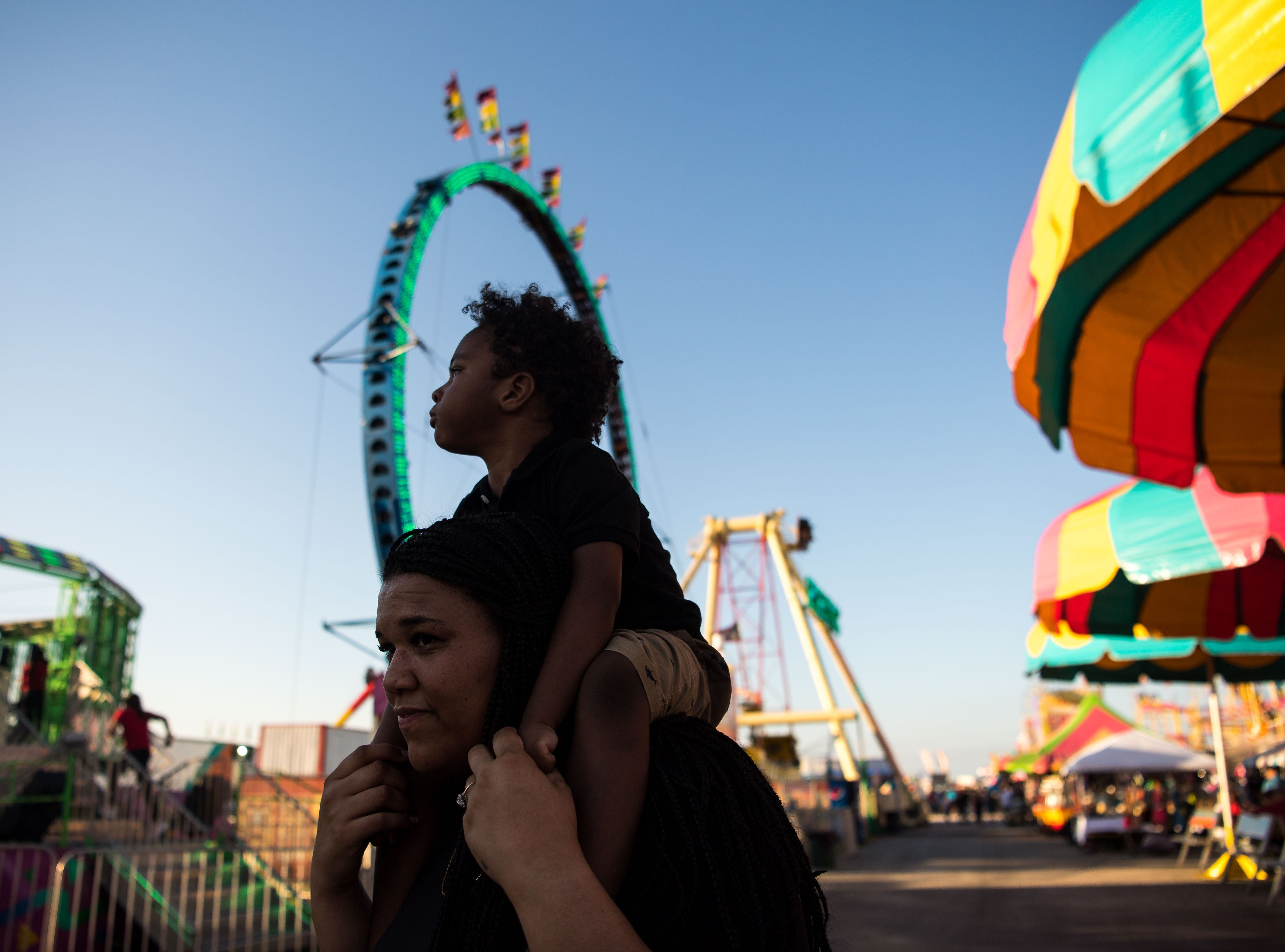 """Nathan Anyaorah, 2, looks around at the St. Lucie County Fair on Fort Pierce on Friday, Feb. 22, 2019, while hoisted on his mother, Dezira Anyaorah, both of Atlanta. """"He's autistic...it's his first time at the fair,"""" Dezira said. """"He loves it — he loves the lights, the music, everybody's running around — he's enjoying it."""""""