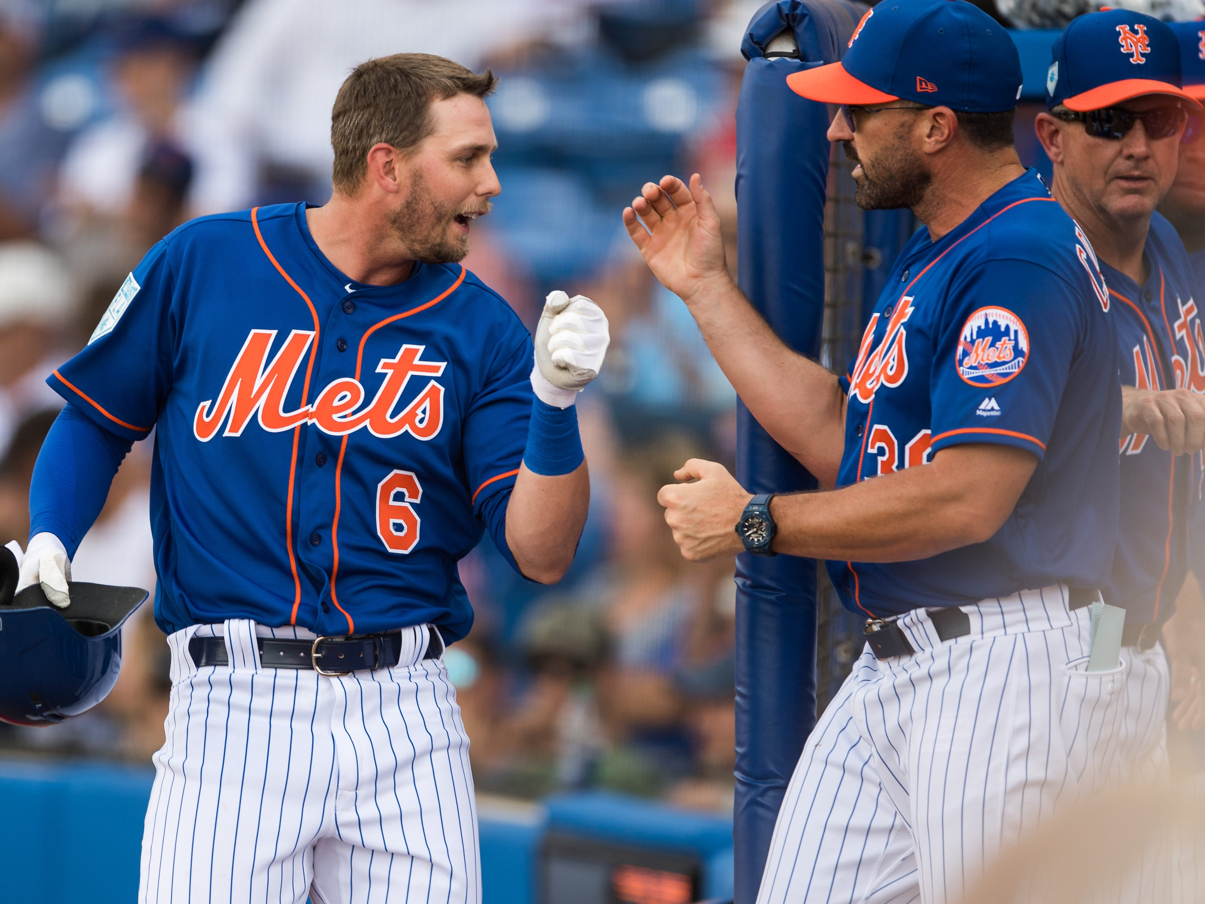 Jeff McNeil (left) with the New York Mets is congratulated by manager Mickey Callaway  after being hit in to score by teammate Robinson Canó, bringing the Mets to a 3-2 lead over the Atlanta Braves in the third inning, during their first spring training game Saturday, Feb. 23, 2019, at First Data Field in Port St. Lucie.