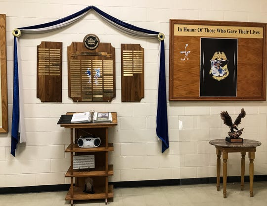 A memorial to fallen Border Patrol agents, right, was destroyed by a sticker that was glued to it. A sticker also was placed on the names of fallen agents at left.