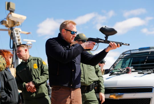 Acting Secretary of Defense Patrick Shanahan fires a modified paintball gun during a tour of the U.S.-Mexico border in Sunland Park, New Mexico, on Feb. 23, 2019. File art