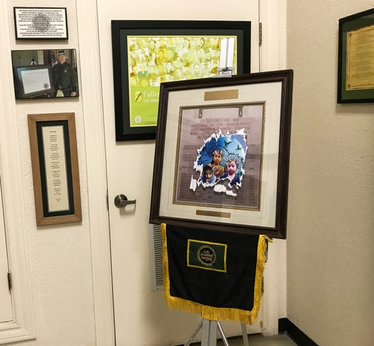 A large sticker showing the faces of children who died in Border Patrol custody is glued to a display that is a memorial to agents who died in the line of duty.