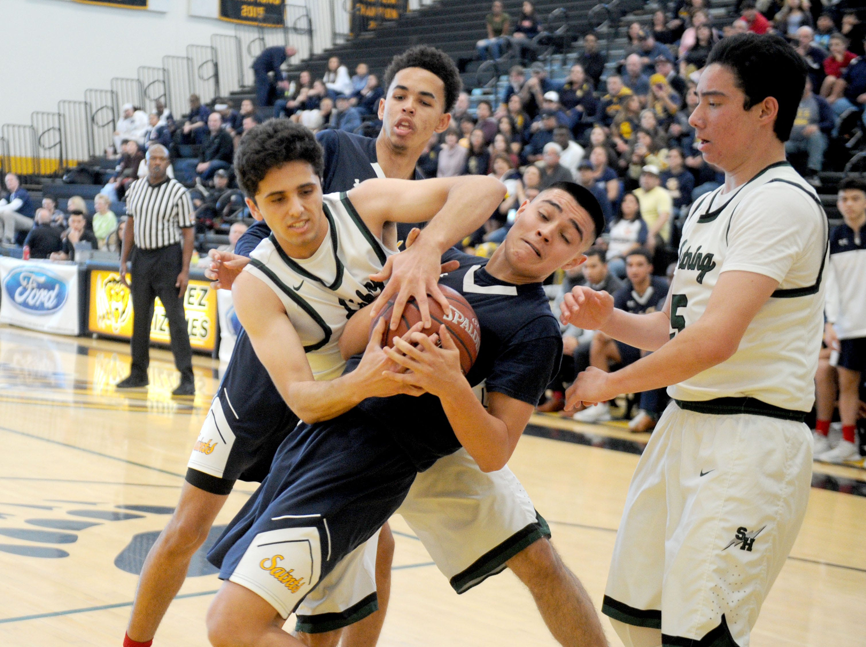 Santa Clara's Ivan Barocio, center, tries to hold onto the ball during the Saints' 68-52 win over Sage Hill in the CIF-SS Division 5AA boys basketball final Saturday at Godinez High in Santa Ana.