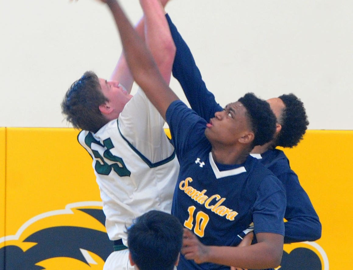 Santa Clara High's Christian Oliver (10) blocks a shot attempt by Sage Hill's Johnny King during the CIF-SS Division 5AA boys basketball final Saturday at Godinez High in Santa Ana. The Saints won 68-52.