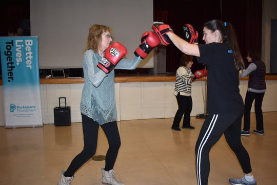 Jennifer Parkinson, right, was diagnosed with Parkinson's disease at the age of 32. Now, she teaches Parkinson's patients how to box as a way to control the disease's progression.