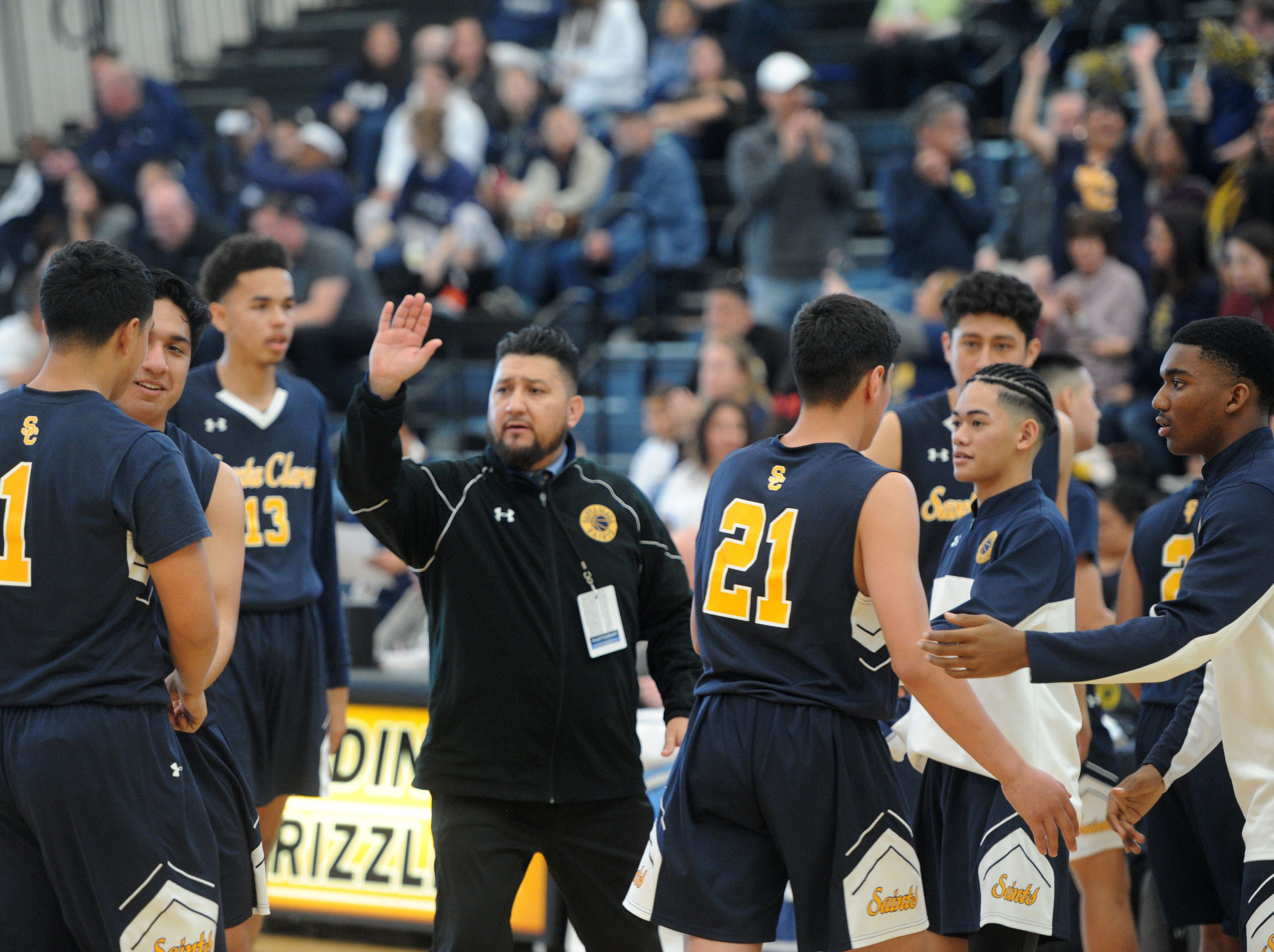 Head coach Bobby Tenorio high-fives his players during Santa Clara's 68-52 victory over Sage Hill in the CIF-SS Division 5AA boys basketball final Saturday at Godinez High in Santa Ana.