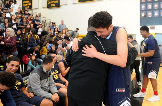 Anthony Juarez hugs head coach Bobby Tenorio after Santa Clara defeated Sage Hill 68-52 to capture the CIF-SS Division 5AA boys basketball title Saturday at Godinez High in Santa Ana.