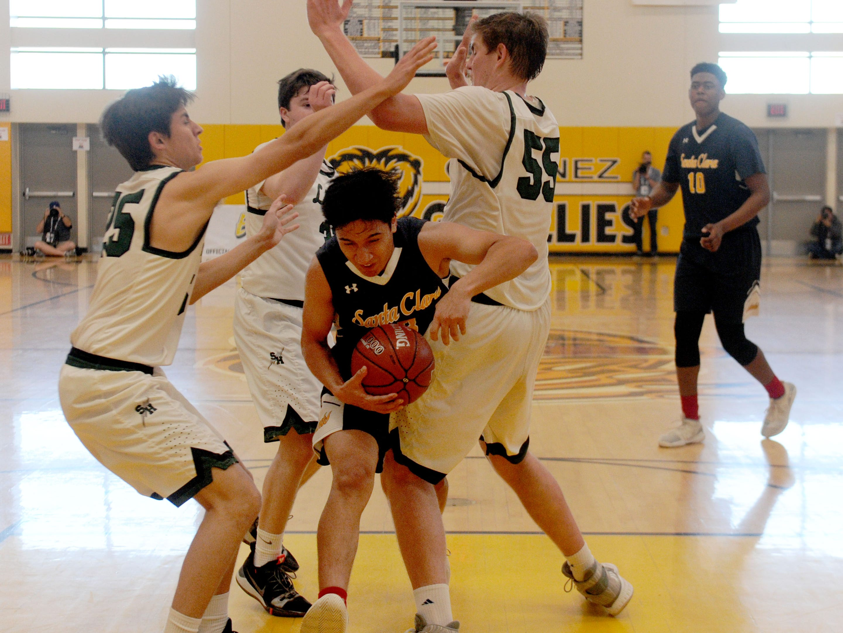 Santa Clara's Felix Ramos tries to squeeze through three Sage Hill defenders during the CIF-SS Division 5AA boys basketball championship game Saturday at Godinez High in Santa Ana. The Saints won, 68-52.