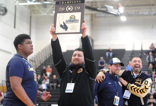 Santa Clara High head coach Bobby Tenorio holds up the championship plaque after the Saints defeated Sage Hill 68-52 to win the CIF-SS Division 5AA boys basketball title Saturday at Godinez High in Santa Ana.