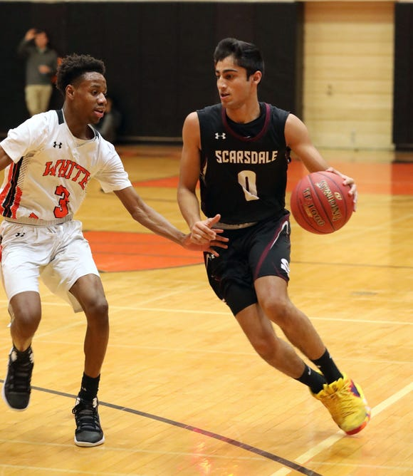 Scarsdale's Jayshen Saigal moves the ball in front of White Plains' Mehki Woodbury during their Class AA quarterfinal at White Plains High School, Feb. 23, 2019. White Plains beat Scarsdale, 69-65 in overtime.