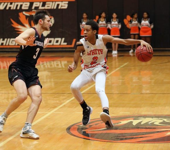 White Plains' Eisaiah Murphy moves the ball in front of Scarsdale's Eitan Altman, during their Class AA quarterfinal at White Plains High School, Feb. 23, 2019. White Plains beat Scarsdale, 69-65 in overtime.