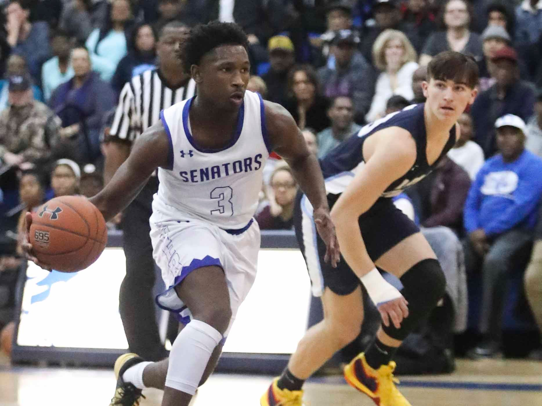 Dover's Eden Davis (left) moves toward the hoop as Lake Forest's Nathan McGray defends in Dover's win in the Henlopen Conference title game at Dover High School Friday.