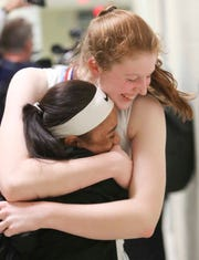 Cape Henlopen's Abby Hearn (right) hugs teammate Dania Cannon after the Vikings won the Henlopen Conference girls basketball championship game with a 56-42 win over Woodbridge on Friday night at Dover High.